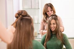 Cute girl happy with her hairdo at hair salon. Looking at her reflection in the mirror, during professional female hair stylist is working on creative hair bun royalty free stock photos