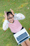 Cute girl is happy with notebook on grass Royalty Free Stock Images