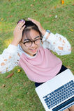 Cute girl is happy with notebook on grass Stock Images
