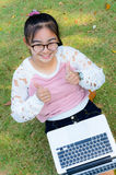 Cute girl is happy with notebook on grass Royalty Free Stock Photo