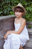 Cute girl in a hat sitting on the porch Royalty Free Stock Photo