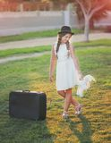 Cute girl in a hat and with a suitcase Stock Images