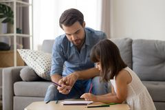 Cute girl have fun drawing picture with dad. Little cute daughter enjoy spending time at home with young dad drawing with colorful pencils together, father and royalty free stock photo