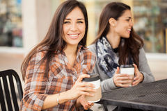 Cute girl having coffee with some friends. Portrait of a gorgeous Hispanic young women hanging out with her friends and enjoying a cup of coffee Stock Image
