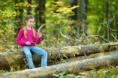 Cute girl having fun during forest hike on beautiful summer day. Active family leisure with kids. Royalty Free Stock Photography