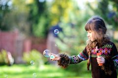 Cute girl having fun with soap bubbles outdoors Stock Photos