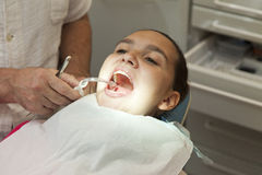 Cute girl having her teeth checked by doctor Stock Image