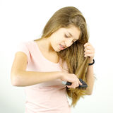 Cute girl having trouble brushing tangled long hair. Unhappy teenager brushing hair smiling with braces Stock Photo