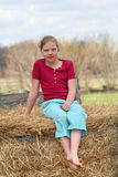 Cute girl on hay bale Stock Photography