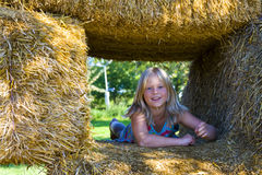 Cute girl on haybales. A cute girl relaxing on haybales in a barn Royalty Free Stock Image