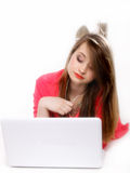Cute girl with headphones and laptop lying Royalty Free Stock Photo