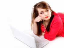 Cute girl with headphones and laptop lying Royalty Free Stock Photography