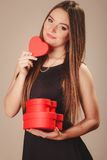 Cute girl with hearts. Love help and charity concept. Young beauty cute long haired woman girl in black dress holding hearts boxes gifts in studio Royalty Free Stock Photo