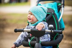 Cute girl in heat riding her tricycle in spring park. Cute baby girl in heat riding her tricycle in spring park Royalty Free Stock Image