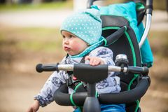 Cute girl in heat riding her tricycle in spring park. Cute baby girl in heat riding her tricycle in spring park Stock Image