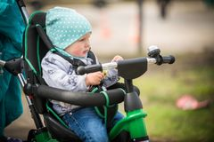 Cute girl in heat riding her tricycle in spring park. Cute baby girl in heat riding her tricycle in spring park Royalty Free Stock Photography