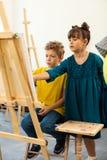 Cute girl helping her classmate painting in art school stock image