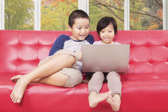 Cute girl and her brother using laptop at home Royalty Free Stock Images