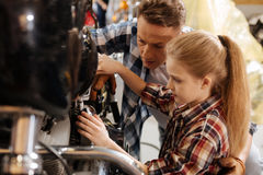 Cute girl and her dad fixing bike together Stock Photos