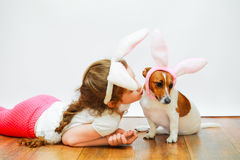 Cute girl and her friend dog. With bunny ears sit on wooden floor on  light wall background Stock Photo