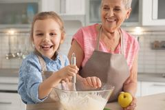 Cute girl and her grandmother cooking stock images