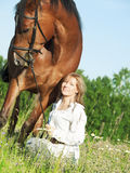 Cute girl  with her horse in the blossom field Stock Photo