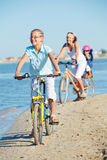 Cute girl with her mother and brother ride bikes Royalty Free Stock Image