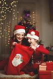 Cute girl and her mother on a Christmas/New Year's Eve, opening presents Royalty Free Stock Photo