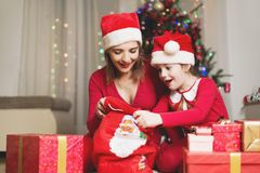 Cute girl and her mother on a Christmas/New Year's Eve, opening presents Royalty Free Stock Photography