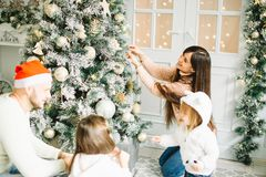 Happy girl decorating Christmas tree.Family, christmas, ,happiness concept Stock Photos