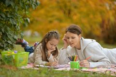 Cute girl with her mother doing homework stock images