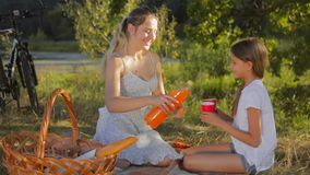 Cute girl with her mother drinking orange juice on the picnic at park stock video
