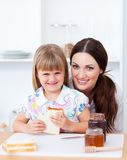 Cute girl and her mother eating slices of bread Stock Photos