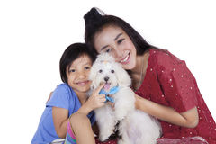 Cute girl and her mother holding dog in studio Royalty Free Stock Photos