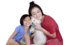 Cute girl and her mother hug maltese dog Stock Photos
