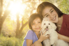 Cute girl and her mother hugging puppy Royalty Free Stock Images
