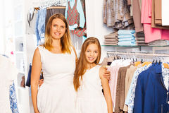 Cute girl with her mother in white outfit at shop Royalty Free Stock Image