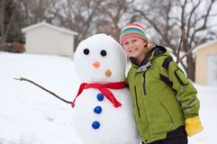 Cute Girl and Her Snowman. Cute Girl Poses Next to the Snowman She Made Stock Images