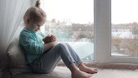 Cute girl with her toy bear. Sitting on window sill stock video
