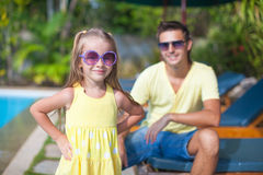 Cute girl with her young dad near swimming pool Stock Photography