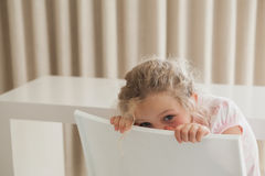 Cute girl hiding face behind chair. Portrait of a cute young girl hiding face behind chair in the house Stock Photography