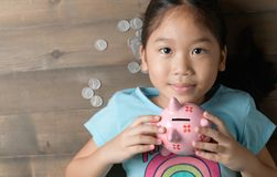 Cute girl hold a pig bank on the vintage wood background Stock Photography