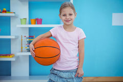 Cute girl holding basket ball Stock Image