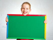 Cute girl holding a blackboard Royalty Free Stock Photography
