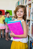 Cute girl holding books in school library Royalty Free Stock Photo