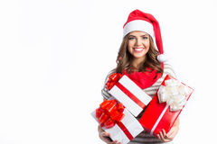 Cute girl holding a Christmas and New Year gifts. Christmas girl in santa hat with boxes. Royalty Free Stock Photos