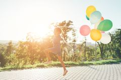 Cute girl holding colorful balloons in the city park, playing, r. Unning, jumping against blue sky, clouds and trees, spreading hands up. Children playing stock photo
