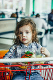 Cute girl holding containers with healthy food in arms sitting in a shopping cart. Cute girl holding containers with healthy food in arms sitting in a shopping Stock Images