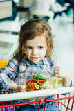 Cute girl holding containers with healthy food in arms sitting in a shopping cart. Cute girl holding containers with healthy food in arms sitting in a shopping Royalty Free Stock Image