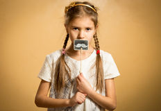 Cute girl holding funny decorative mustaches Royalty Free Stock Photography